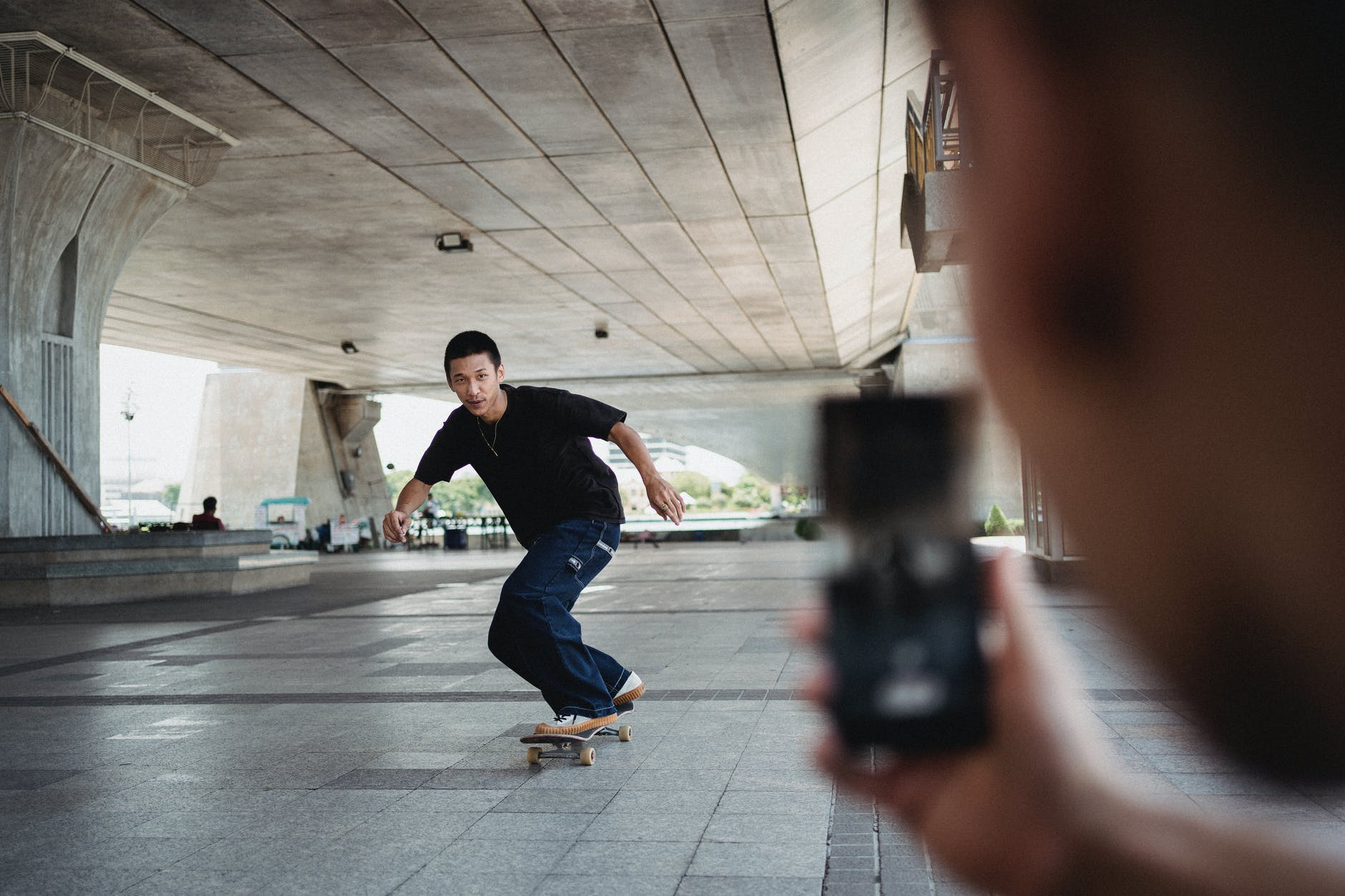 crop person taking photo of skateboarder